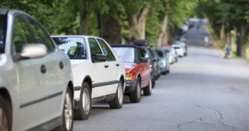Fila de carros estacionados com Zona Azul App próximo a rua arborizada