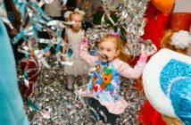Criança se divertindo ao pular o bloco de rua de Carnaval. Ela está rodeada de pessoas, com serpentina e confetes coloridos.